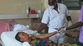 Woman lying in hospital bed treated by doctors