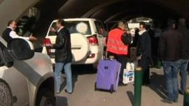 Arab League observers' luggage is wheeled into airport.