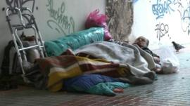 Homeless older man sleeps rough on the streets of Athens.