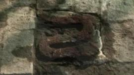 A plaque with a representation of a serpent carved into it