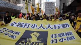People hold a large black and yellow banner in Hong Kong.