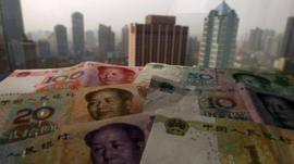 Yuan banknotes against Shanghai skyline