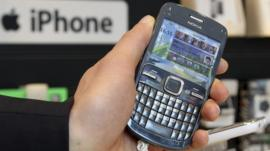 A Nokia mobile phone is pictured near an iPhone logo in a shop in Brussels.
