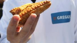 Greggs employer holding a pasty