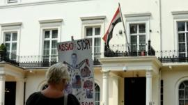 A protester holds a sign outside the Embassy of the Syrian Arab Republic in central London