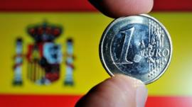 A coin of euro with a Spanish national flag