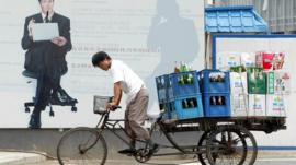 A man hauls a tricycle load of beer in Beijing's central business district, China