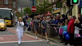 Woman carries the Olympic torch through Dumfries