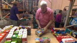 Food bank staff packaging parcels in Swindon warehouse
