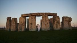 Michael Johnson holds Olympic torch at Stonehenge