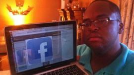 Robert Collins holding his laptop