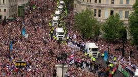 Crowds gather to cheer on British Olympic and Paralymic athletes on through their parade of London