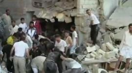 Syrians looking through rubble in Aleppo
