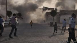 Smoke rises over the streets after a shell landed from Syria in the Turkish border village of Akcakale, south-eastern Sanliurfa province, 3 October 2012