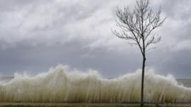 Waves come over sea wall on Long Island, New York