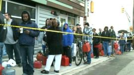People wait in a queue to buy petrol