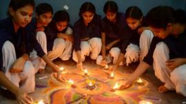 Indian school girls lighting candles as they sit near a