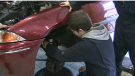 Trainee mechanic works on a car