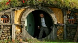 Director Sir Peter Jackson emerges from from a Hobbit house