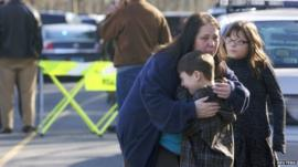 A young boy is comforted outside Sandy Hook Elementary School after a shooting in Newtown, Connecticut