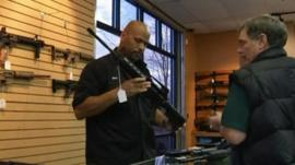 Gun store salesman showing customer an AR 15-style rifle