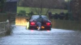 A man pushing his car through flood water