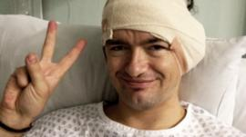 William Mager in hospital post surgery with bandage round his head. He is making a peace sign.
