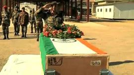 Coffin of Indian soldier being saluted