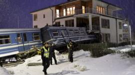 Police guard the scene where a train hit a house in a Stockholm suburb, 15 January