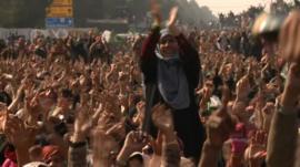 Woman sitting on shoulders of man in huge crowd