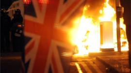 Union flag in front of riot fire