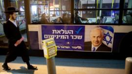 People walk past Netanyahu poster