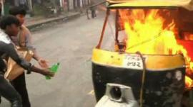 Protesters putting a tuk tuk on fire