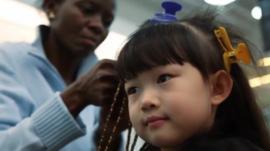 Chinese girl has her hair braided in Beijing