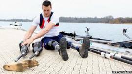 Paralympic rower Nick Beighton sits by the river next to his boat wearing prosthetic limbs