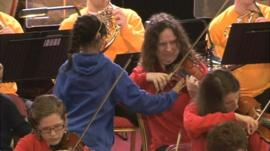 Deaf child touching violin