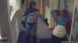 Man in Batman outfit in police station