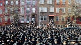 Orthodox Jewish mourners gather outside a synagogue in Brooklyn