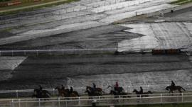 Horses and jockeys make their way past ground sheeting covering the course