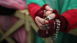 A woman holds rosary beads