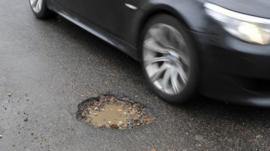 A car passing a pothole