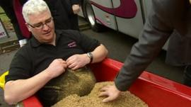 Coach driver Paul Johnston sitting in a bath of maggots