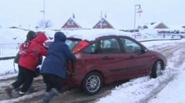 People push a car