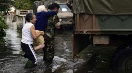 A soldier evacuates an elderly woman in a flooded street in La Plata