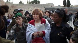Israeli policewomen detain a member of the religious group