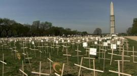 A temporary memorial of wooden crosses on the grass of the National Mall