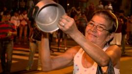 Lady hitting a saucepan in protest at the election