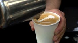 A barista preparing a cafe latte