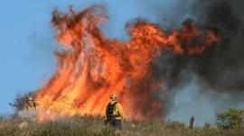 Fire fighters set fires to burn off dry brush to protect homes