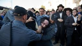 Israeli police officers arrest an ultra-Orthodox protestor objecting to the religious group